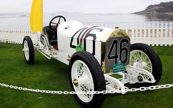 The 1908 Mercedes-Benz race car of Prinz Heinrich positioned on the 18th hole of the Pebble Beach Golf Course with a beautiful view of Monterey Bay.
