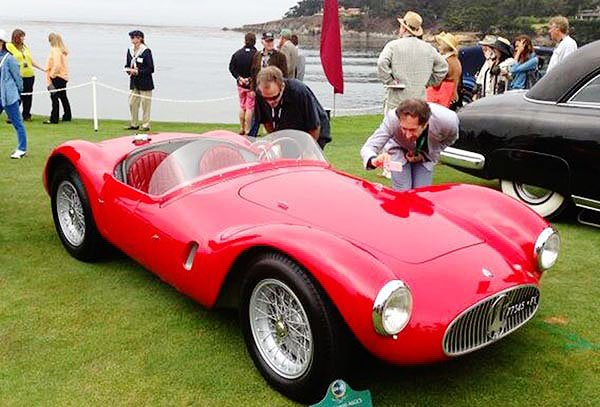 As the fog rolled out onto the bay, fans were already out to appreciate the fine automotive specimens at the Pebble Beach Concours D'Elegance. Here spectators are getting their closeup shots of a 1955 Maserati.